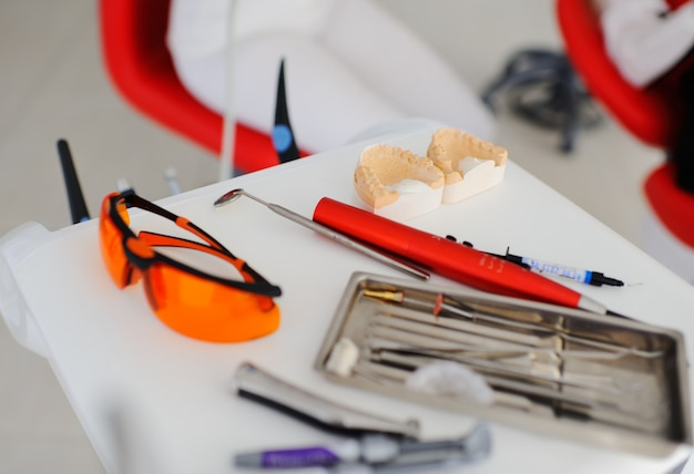 Instrumentos odontológicos no fundo do dentista e paciente