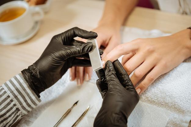 Instrumentos para manicure. artista experiente em unhas usando luvas pretas e usando instrumentos para manicure