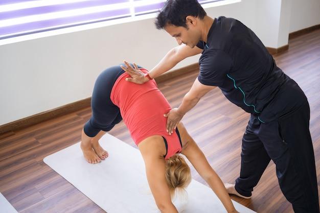 Instrutor ajudando a mulher a fazer pose de cachorro virada para baixo