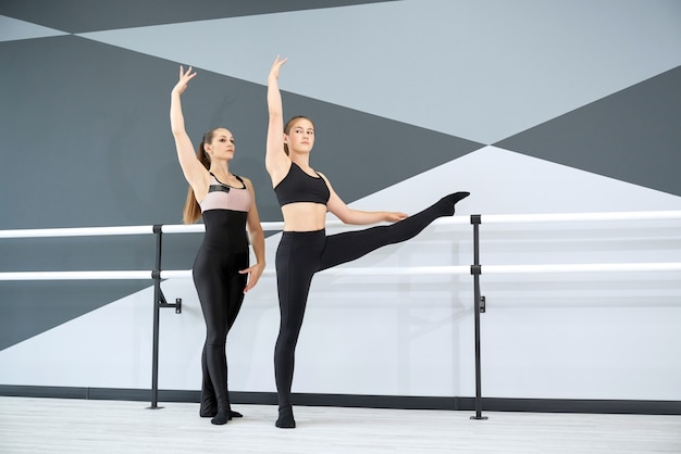 Instrutor ajudando menina a aprender o movimento coreográfico