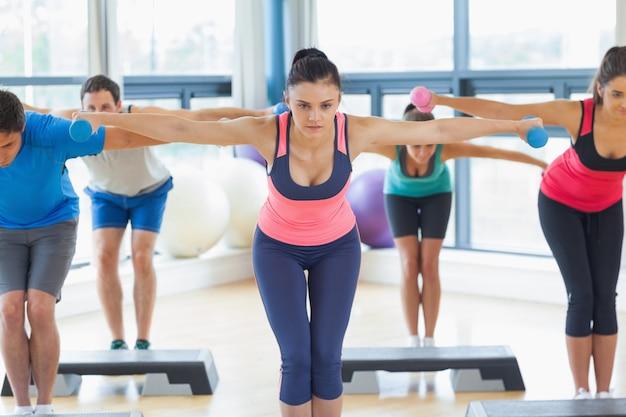 Instrutor, com, classe aptidão, executar, passo, aeróbica, exercício, com, dumbbells