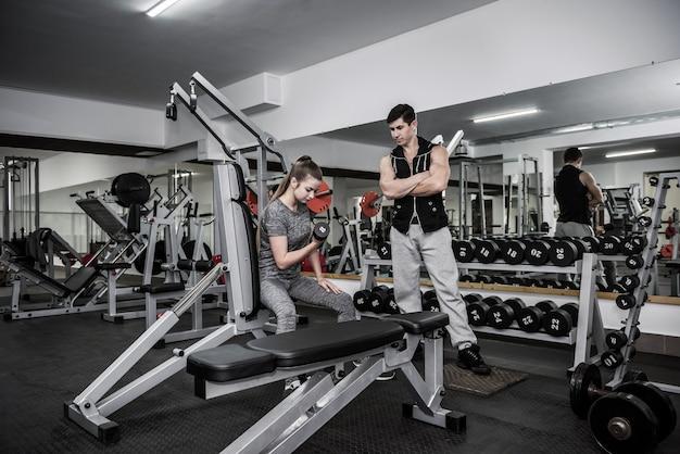 Instrutor controlando como mulher fazendo exercícios com halteres