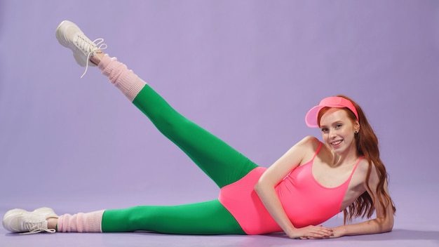 Instrutor de aeróbica feminino sexy jovem fazendo exercícios aeróbicos