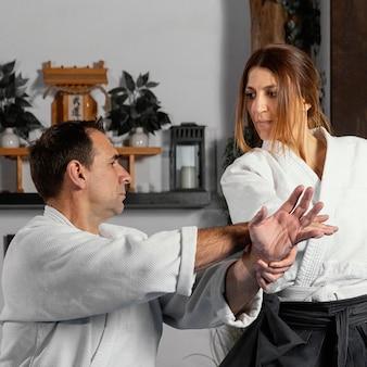 Instrutor de artes marciais e estagiária praticando juntos