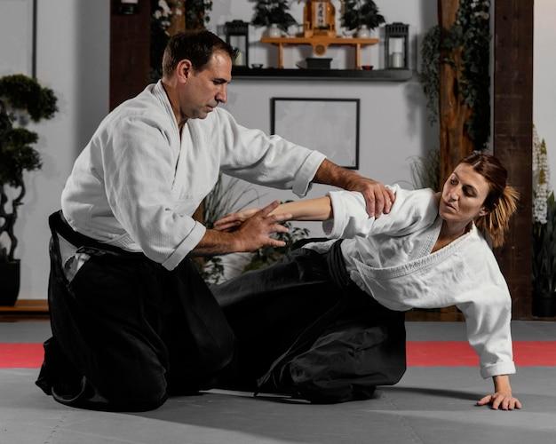 Instrutor de artes marciais e estagiária praticando