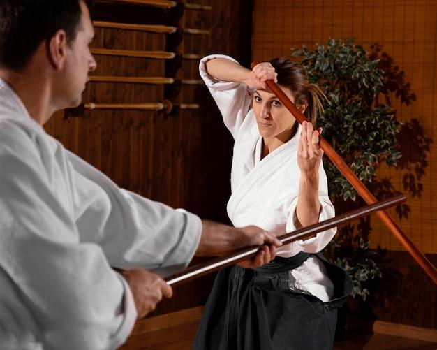 Instrutor de artes marciais na sala de prática com uma vara de madeira e estagiária