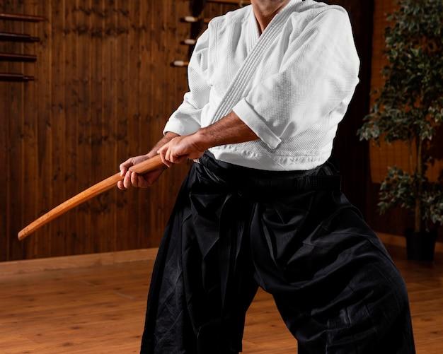 Instrutor de artes marciais na sala de prática com uma vara de madeira
