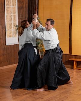 Instrutor de artes marciais na sala de prática, treinando com estagiária