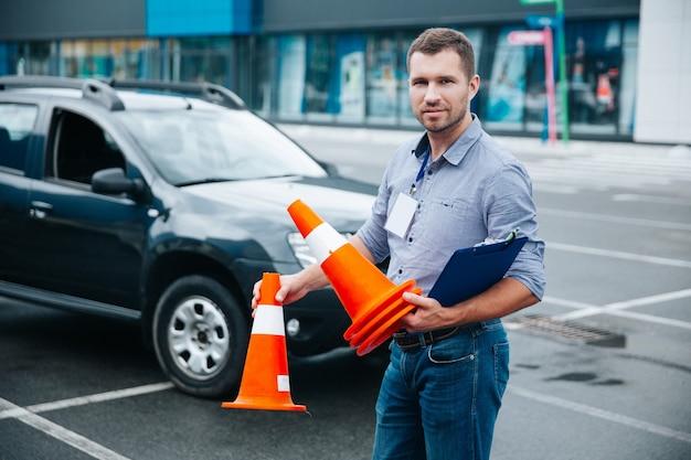 Instrutor de direção coletando cones de plástico