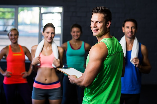 Instrutor de fitness alegre com pessoas no ginásio