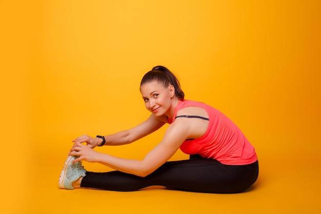 Instrutor de fitness, alongamento de perna, parede amarela