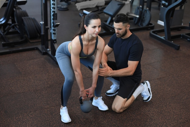 Instrutor de fitness, exercitando-se com seu cliente na academia.