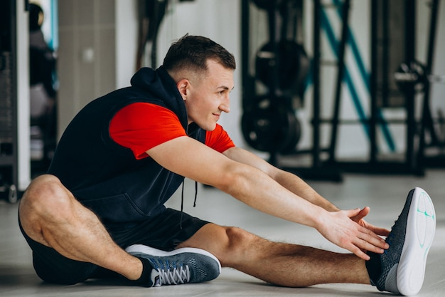 Instrutor de fitness jovem alongamento na academia