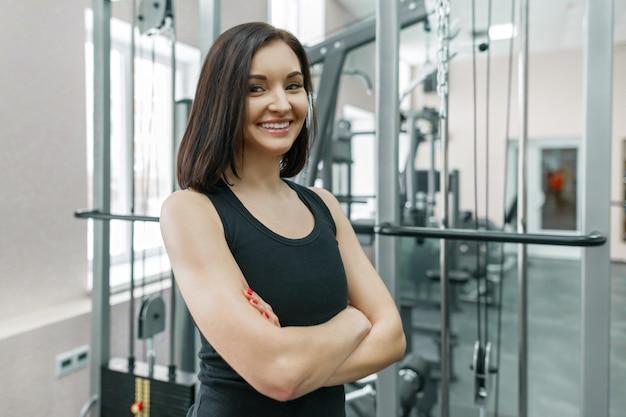 Instrutor de fitness jovem atlética mulher confiante posando no ginásio
