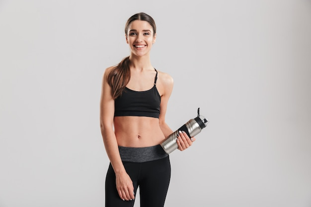 Instrutor de fitness jovem sorridente com agasalho olhando e segurando a garrafa de metal com água parada, isolada sobre a parede cinza
