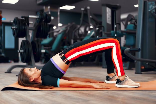 Instrutor de fitness menina bonita, esticando o corpo dela após treino