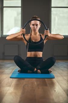 Instrutor de fitness mostra exercícios com um expansor de anel, de manhã na sala de fitness