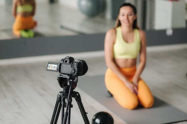 Instrutor de fitness mulher gravando vídeo na câmera durante o treinamento no ginásio coberto. conceito esporte influenciador de estilo de vida e recreação.