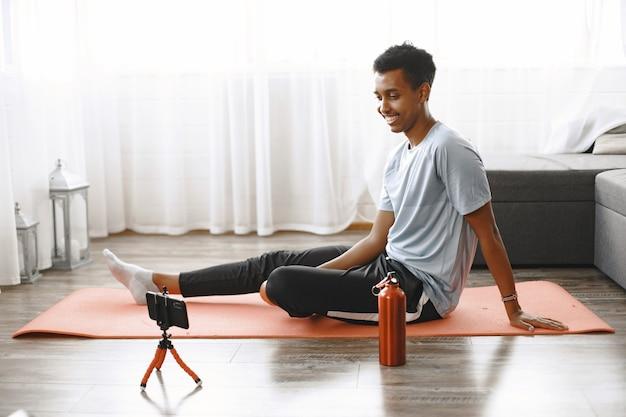 Instrutor de fitness ou blogueiro de vídeo fazendo alongamento. o homem está se filmando na câmera do smartphone em casa.