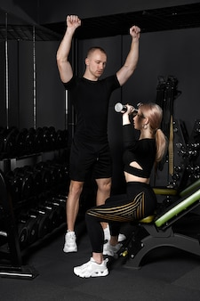 Instrutor de fitness realiza treinamento pessoal para uma garota com halteres na frente do espelho