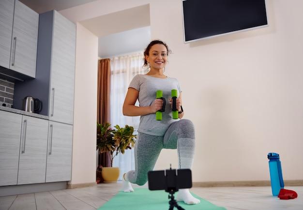 Instrutor de fitness realizando investidas com halteres via telefone celular durante a quarentena. conceito de treino durante o bloqueio