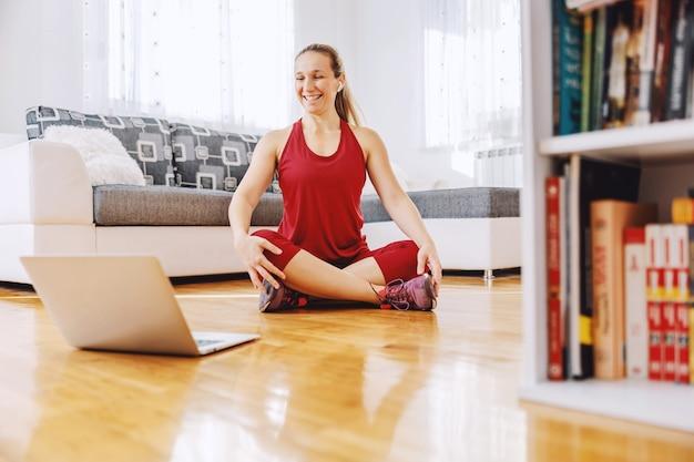 Instrutor de fitness sentado no chão em casa e explicando exercícios para o aluno
