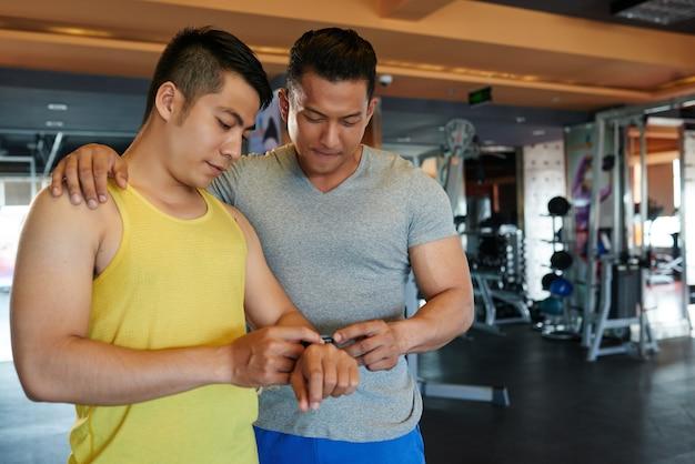 Instrutor de ginástica masculino asiático com a mão no ombro do cliente, olhando para o seu rastreador de fitness