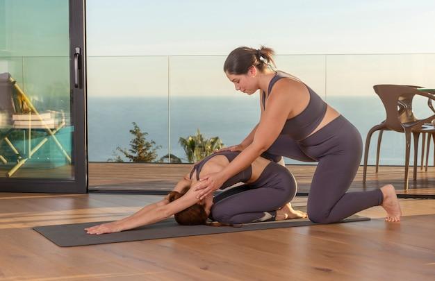 Instrutor de ioga de tiro completo ajudando mulher