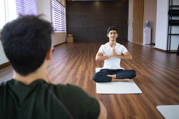 Instrutor de ioga meditando com estudante no ginásio