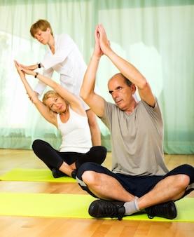 Instrutor de ioga que mostra asana para um casal maduro