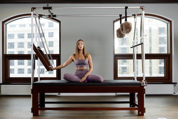 Instrutor de menina no reformador cadillac, posando, mostrando exercícios para correção da coluna vertebral, equipamento moderno do reformador para centros de fitness.