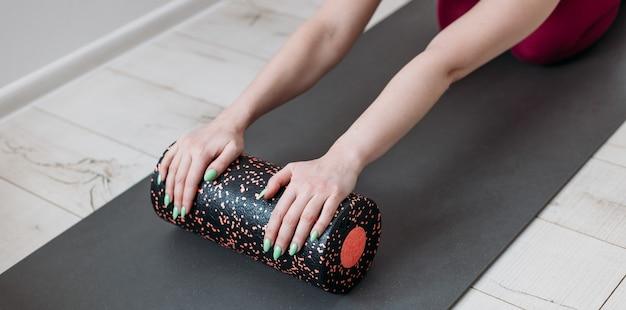 Instrutor de pilates de mulher bonita alongamento e aquecimento usando rolo de espuma, malhando, vestindo roupas esportivas rosa, close-up. esporte e conceito de estilo de vida ativo e saudável.