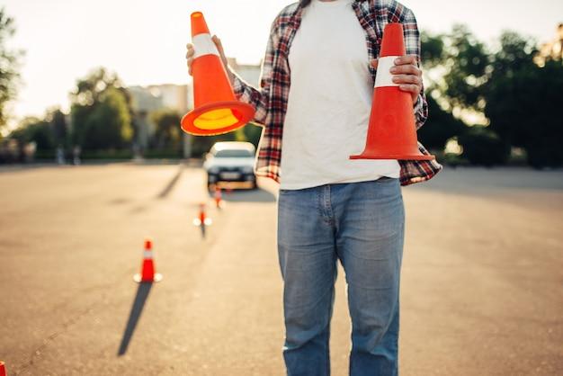 Instrutor de veículo masculino segura cones nas mãos