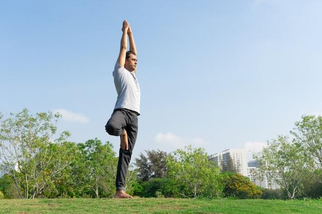 Instrutor de yoga masculino indiano em pose de árvore no gramado verde com arbustos