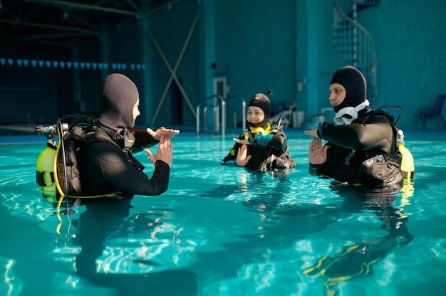 Instrutor e dois mergulhadores, aula em escola de mergulho