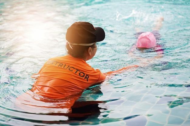 Instrutor feminino ensina criança a nadar.