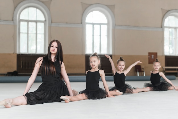 Instrutor feminino, sentando, com, três meninas, ligado, chão, em, classe dança