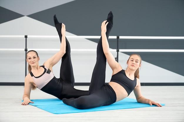 Instrutor feminino sincronizado e alongamento feminino