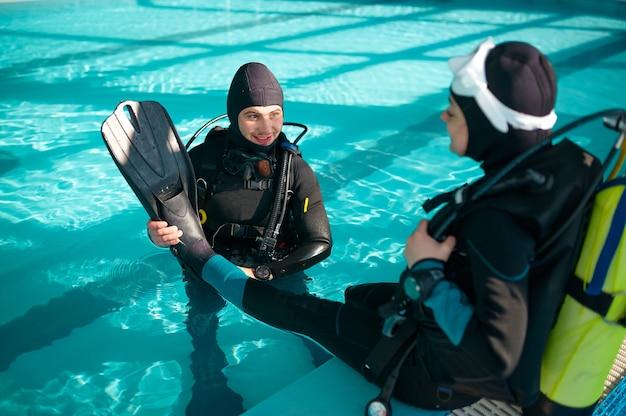 Instrutor masculino ajuda mulher a colocar nadadeiras, mergulho
