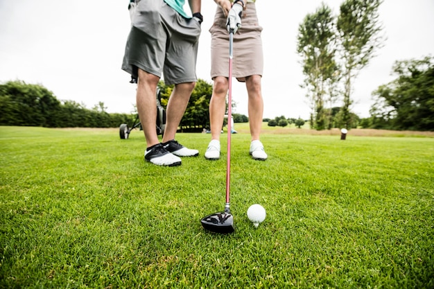 Instrutor masculino, auxiliando a mulher na aprendizagem de golfe