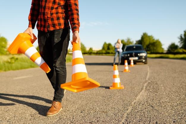 Instrutor masculino coloca cones de trânsito na estrada, escola de condução. homem ensinando a senhora a dirigir o veículo. educação para carteira de habilitação