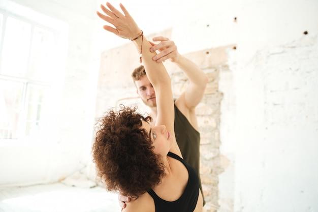 Instrutor masculino da ioga que ajuda a mulher afro-americana