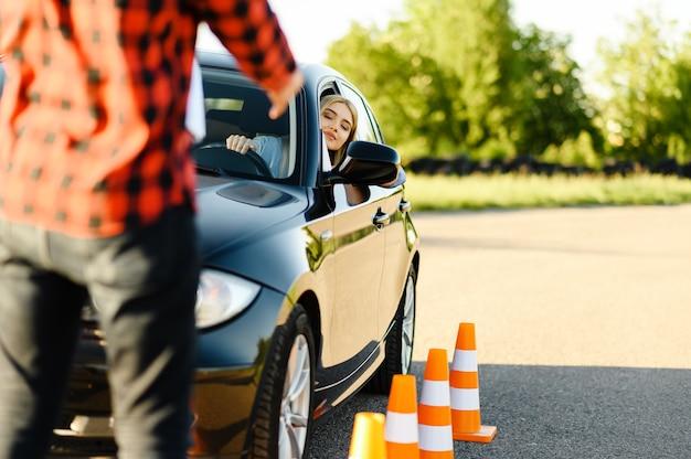 Instrutor masculino e mulher no carro, cones de trânsito, aula de autoescola. homem ensinando a senhora a dirigir o veículo. educação para carteira de habilitação