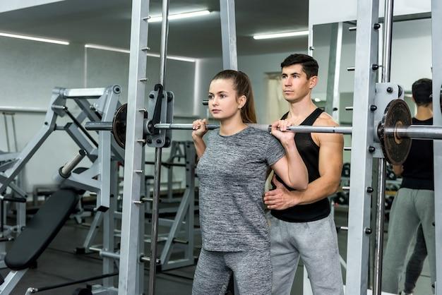 Instrutor pessoal ajudando mulher a levantar halteres