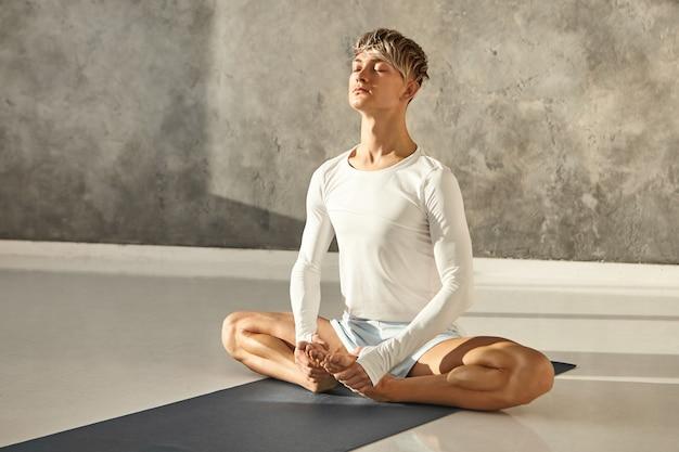 Instrutor profissional de ioga flexível, vestindo camiseta de manga comprida e shorts, sentado descalço no tapete, fazendo pose baddha konasana, fechando os olhos e respirando, com expressão facial calma e pacífica