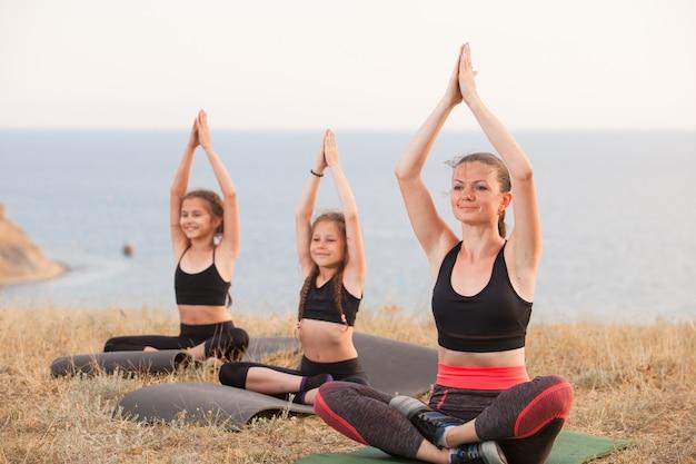 Instrutor treina crianças de ioga nas montanhas no oceano.