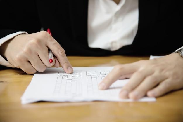 Instrutor verificando o exame de folha de respostas de escolhas múltiplas - pessoas de educação que trabalham com o conceito de teste de papel