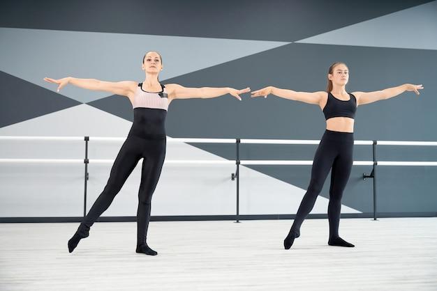 Instrutora e garota sincronizadas em movimentos de aprendizagem