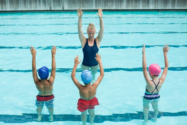 Instrutora ensinando alunos na piscina