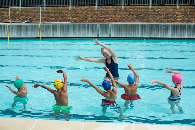 Instrutora ensinando crianças na piscina
